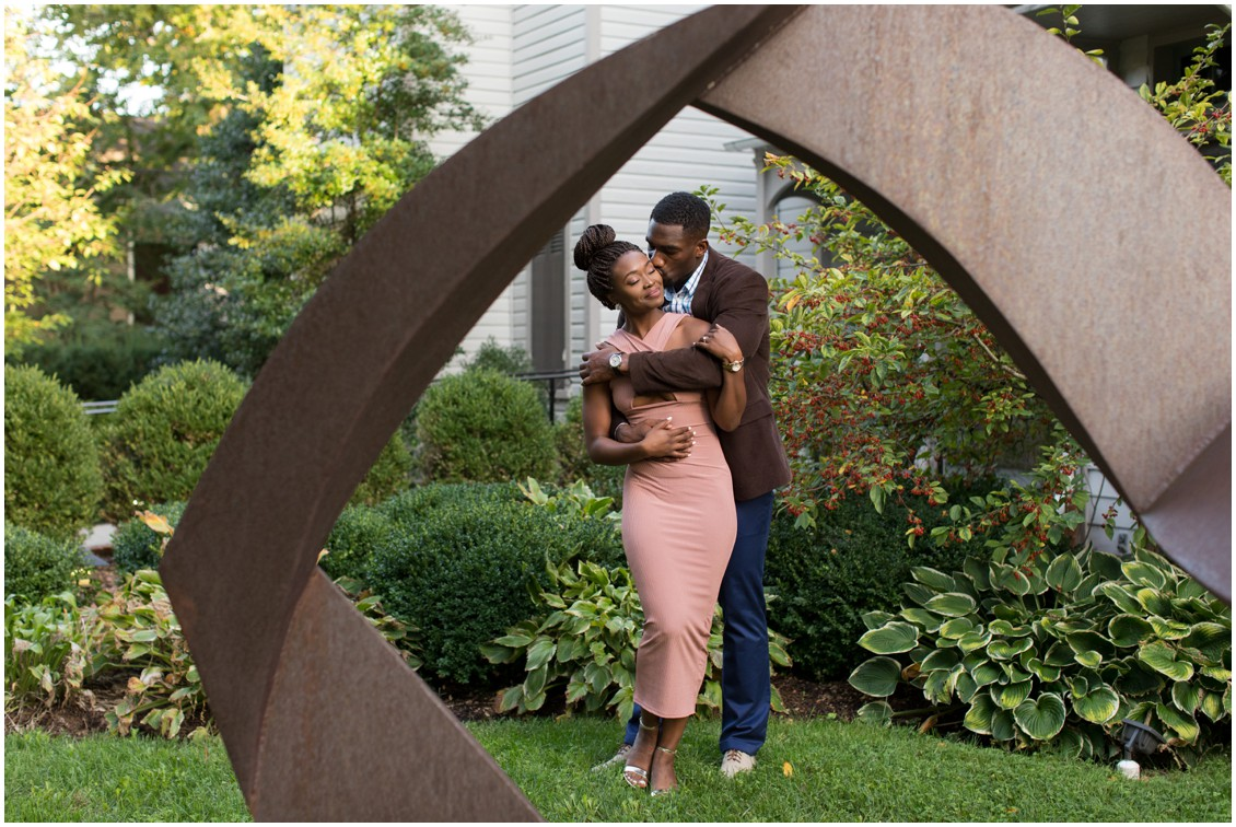 Engaged couple pose near contemporary sculpture in the garden at The Academy of the Arts in Easton, MD