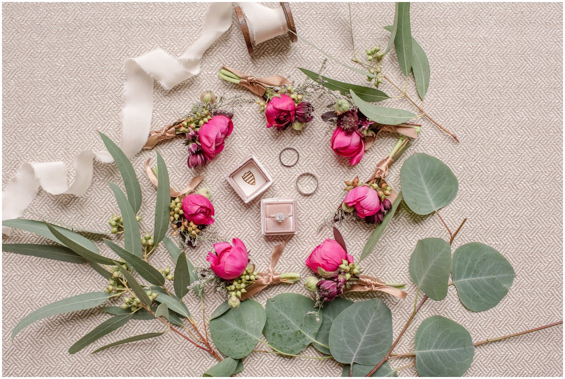 Ribbon, greens, and pink rose boutonnieres surrounding the wedding rings. | My Eastern Shore Wedding |