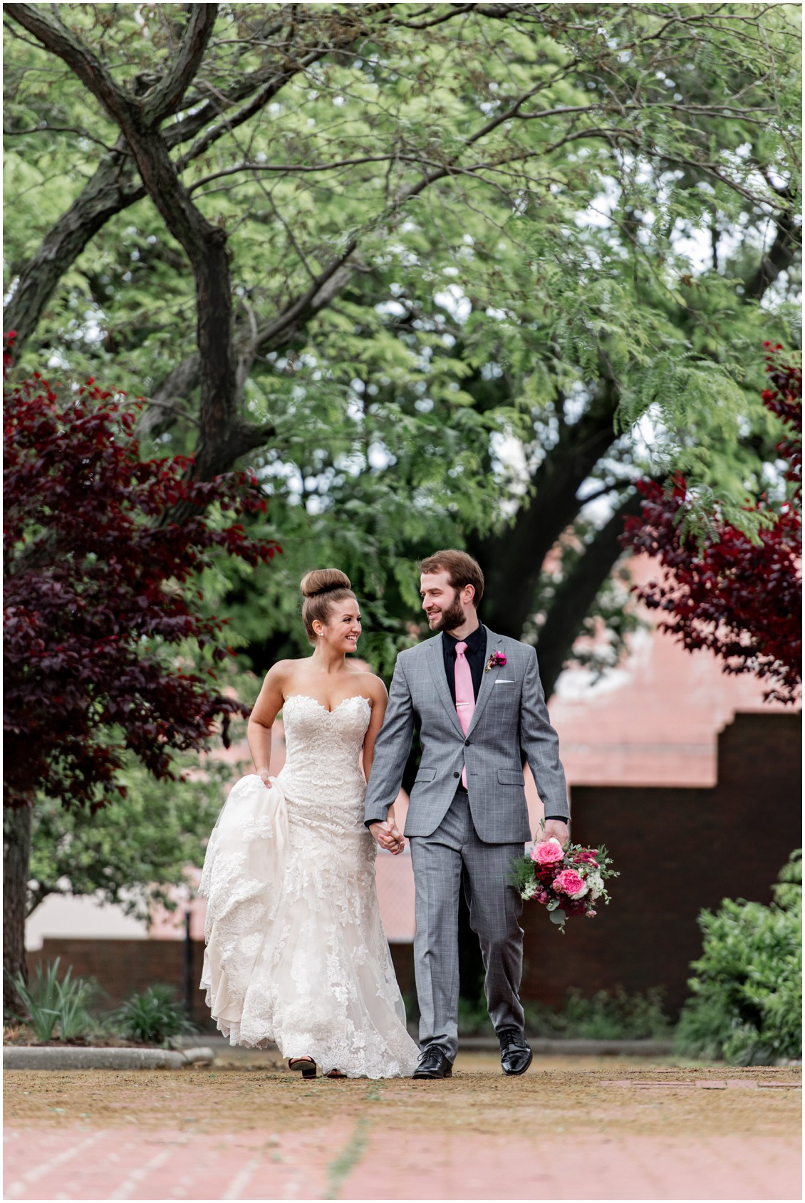 Bride and groom walking hand-in-hand, gray suit with pink tie, and strapless wedding gown. | My Eastern Shore Wedding |