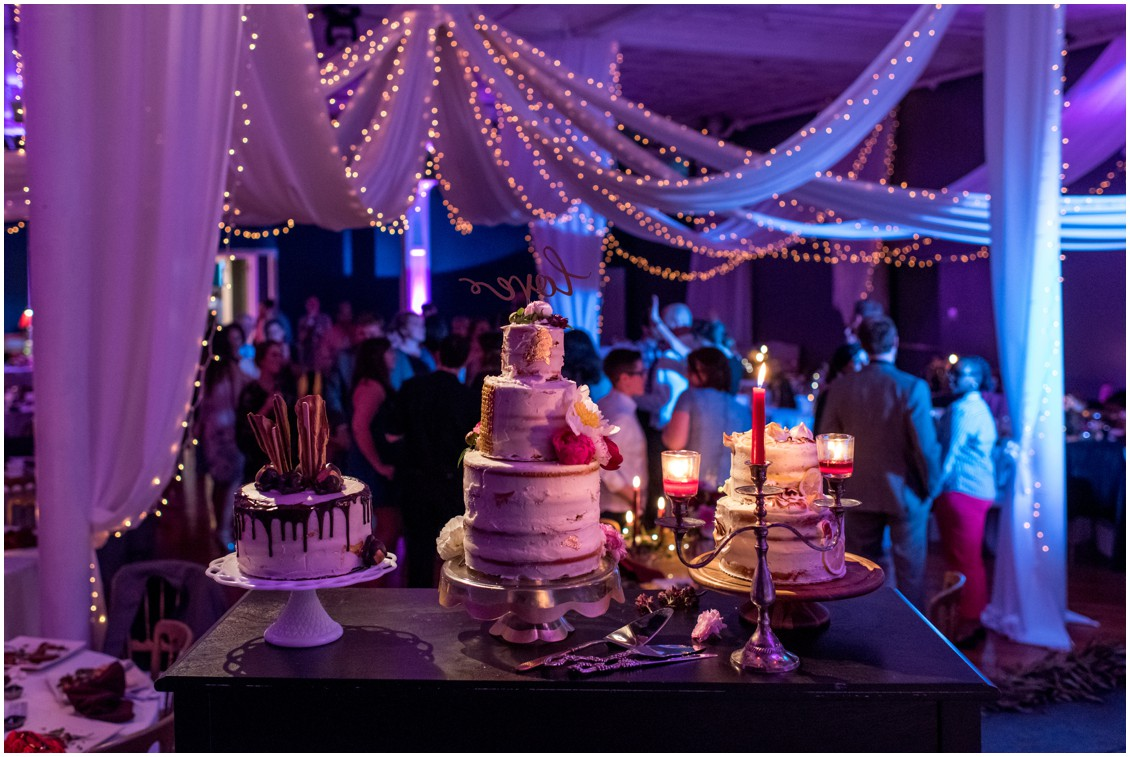Jordan Fichs wedding cakes overlooking the wedding party with a candelabra on the table. | My Eastern Shore Wedding |