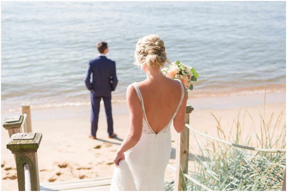 Bride walking up behind groom on the beach for the first look. | My Eastern Shore Wedding |