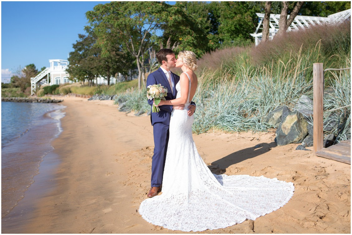 Bride and groom kissing by the water on the beach. | My Eastern Shore Wedding |
