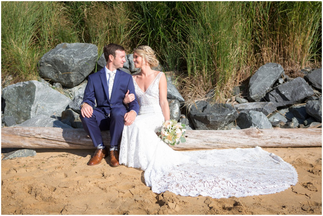 Bride and groom sitting together on a piece of driftwood by the beach. | My Eastern Shore Wedding |