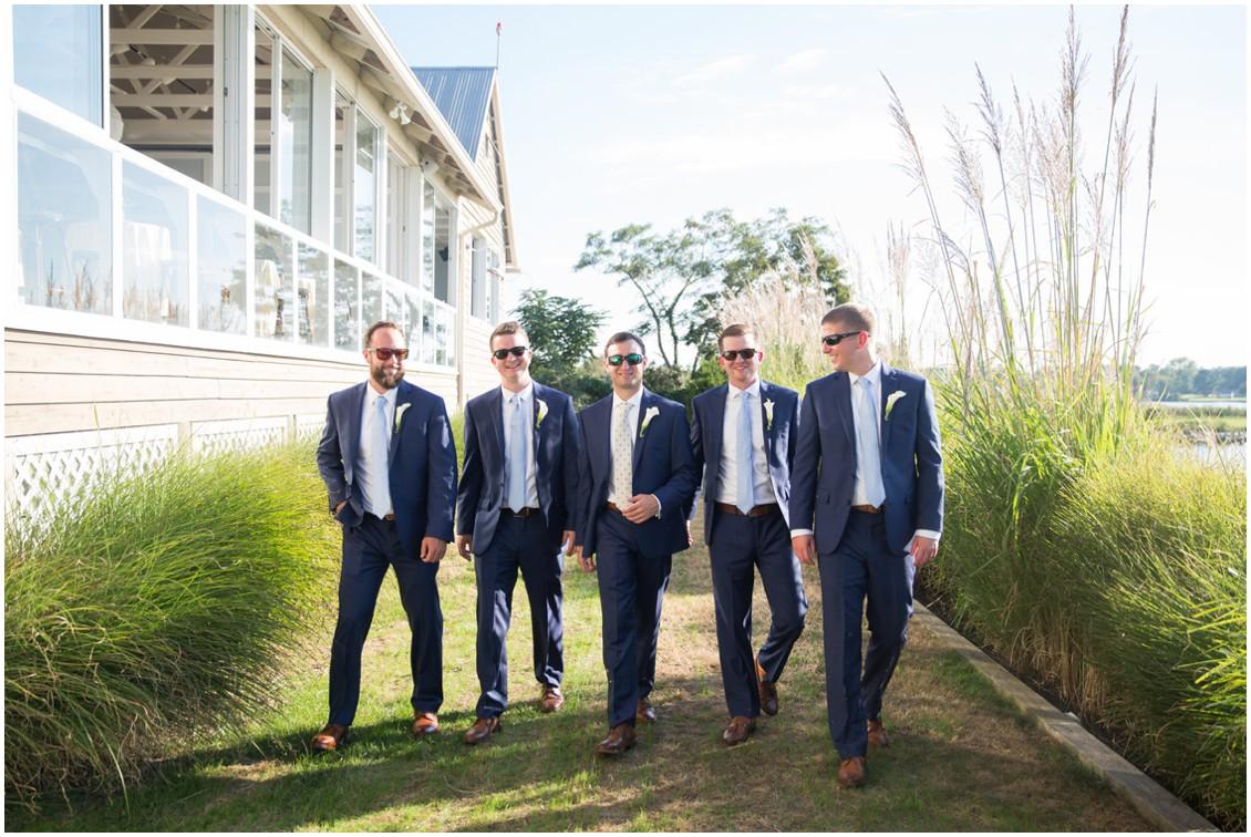 Groom walking with his groomsmen wearing sunglasses in navy suits. | My Eastern Shore Wedding |