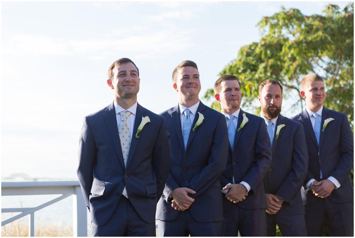 Groom and his groomsmen with lily boutonnières by Lilac & Page, waiting at the altar. | My Eastern Shore Wedding |
