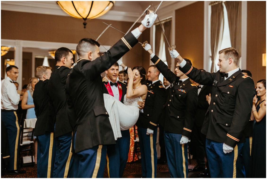 Army groom carries Army bride through saber arch. | My Eastern Shore Wedding |