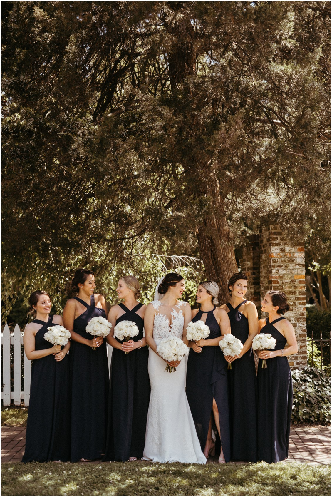 Bride with her bridesmaids under trees, holding bouquets of white peonies. | My Eastern Shore Wedding |