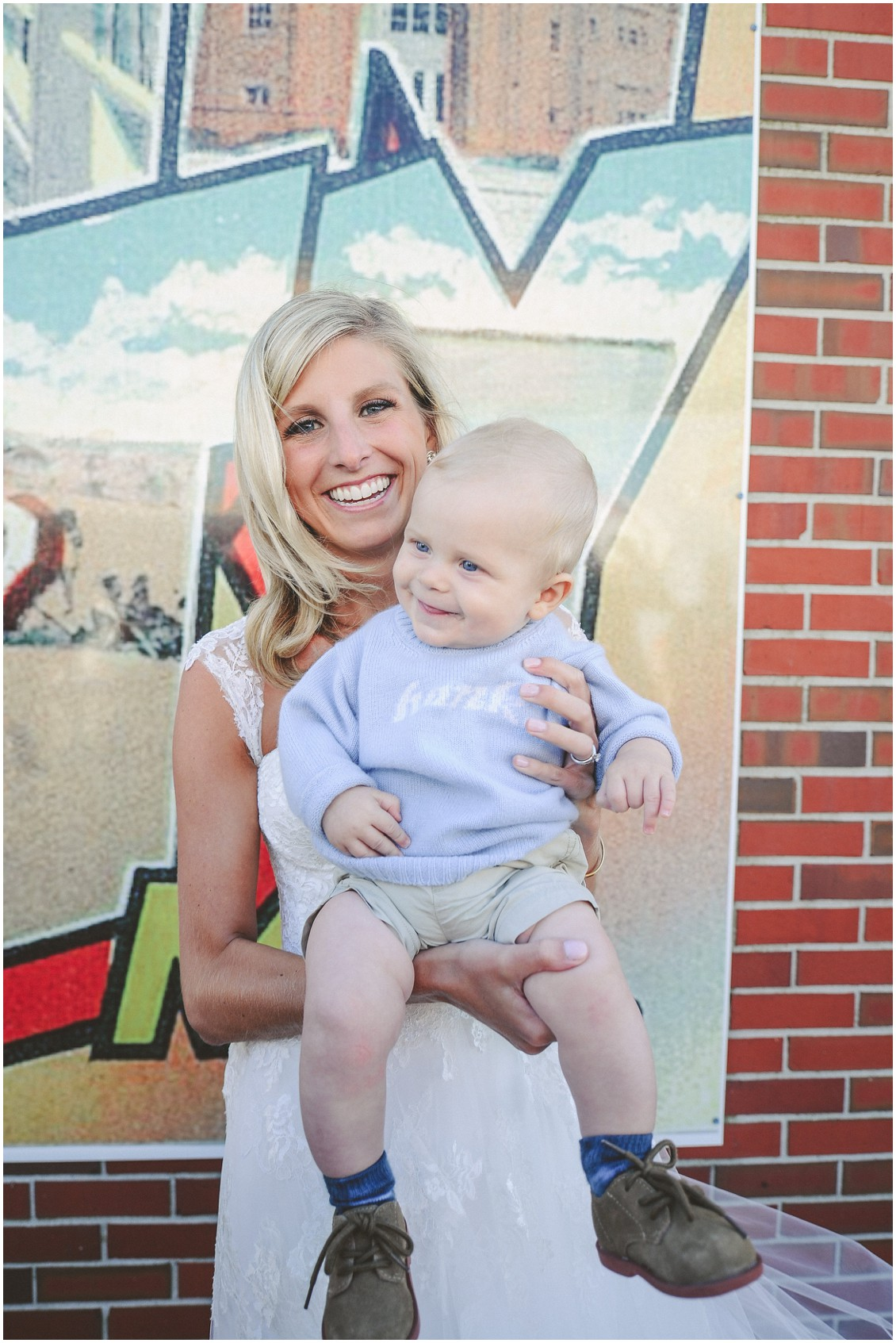 "Bride with baby in front of ""Greetings From Ocean City"" sign. 