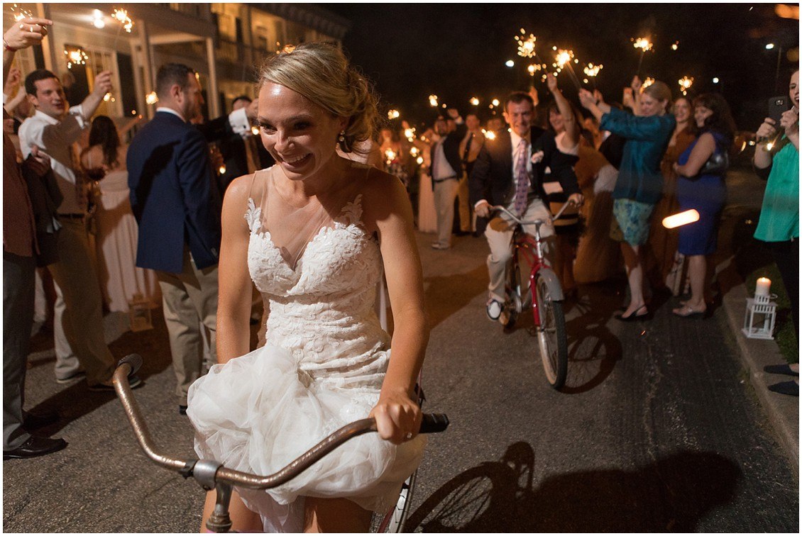 Bride and groom riding out of the reception on bicycles, guests holding sparklers over them at the Historic Kent Manor Inn in Stevensville, MD. | My Eastern Shore Wedding |