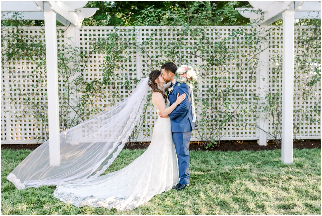 Bride and groom kiss in front of vine covered lattice wall. | My Eastern Shore Wedding |