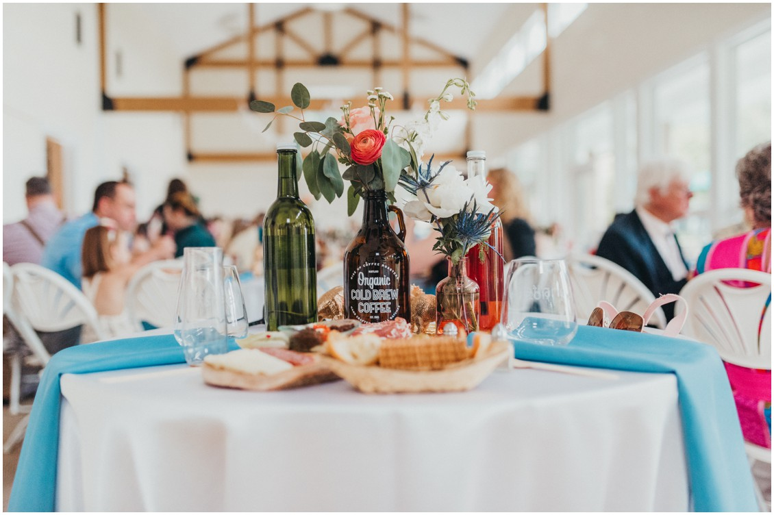 Multi-colored wine and coffee glass bottles with flowers. | My Eastern Shore Wedding |