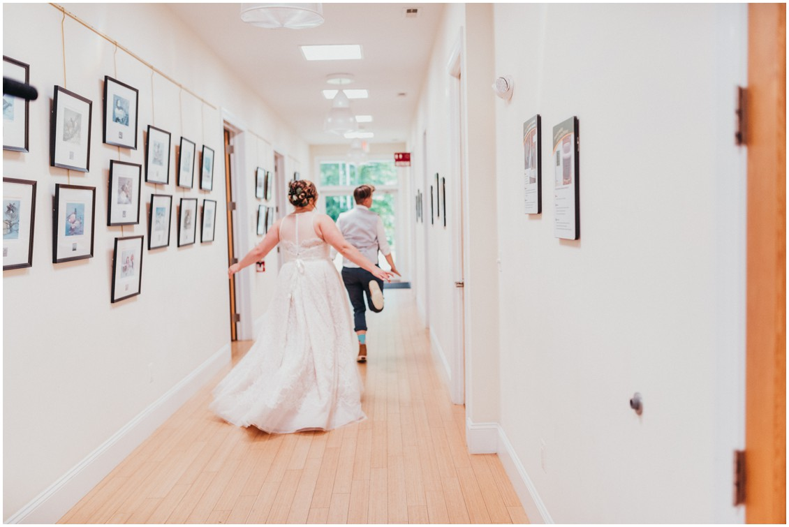 Married couple leaving reception together, running down the hall. | My Eastern Shore Wedding |