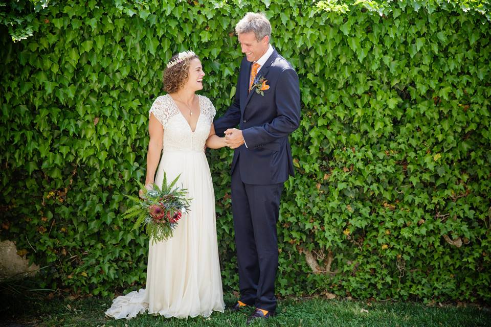 Bride holds her tropical inspired bouquet with Groom smiling in-front of an ivy wall