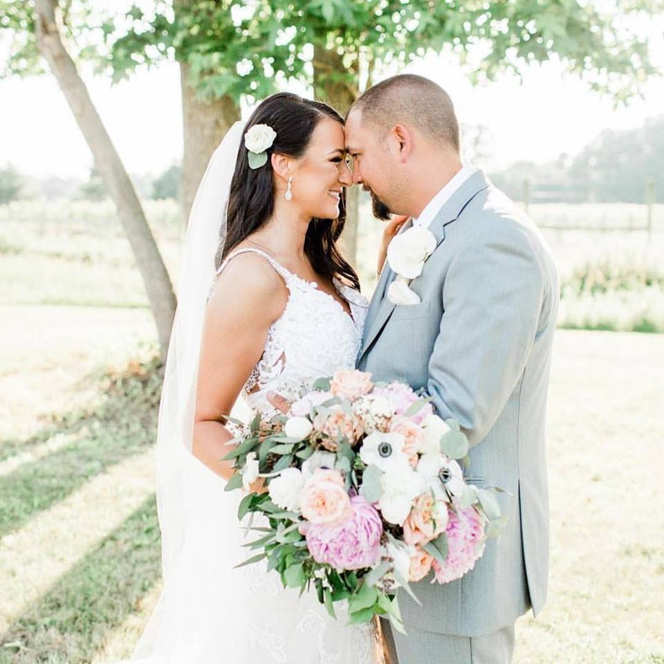 Young Bride and Groom face each other while showing off pink, peach, white and green Bridal Bouquet by Chesapeake Blooms