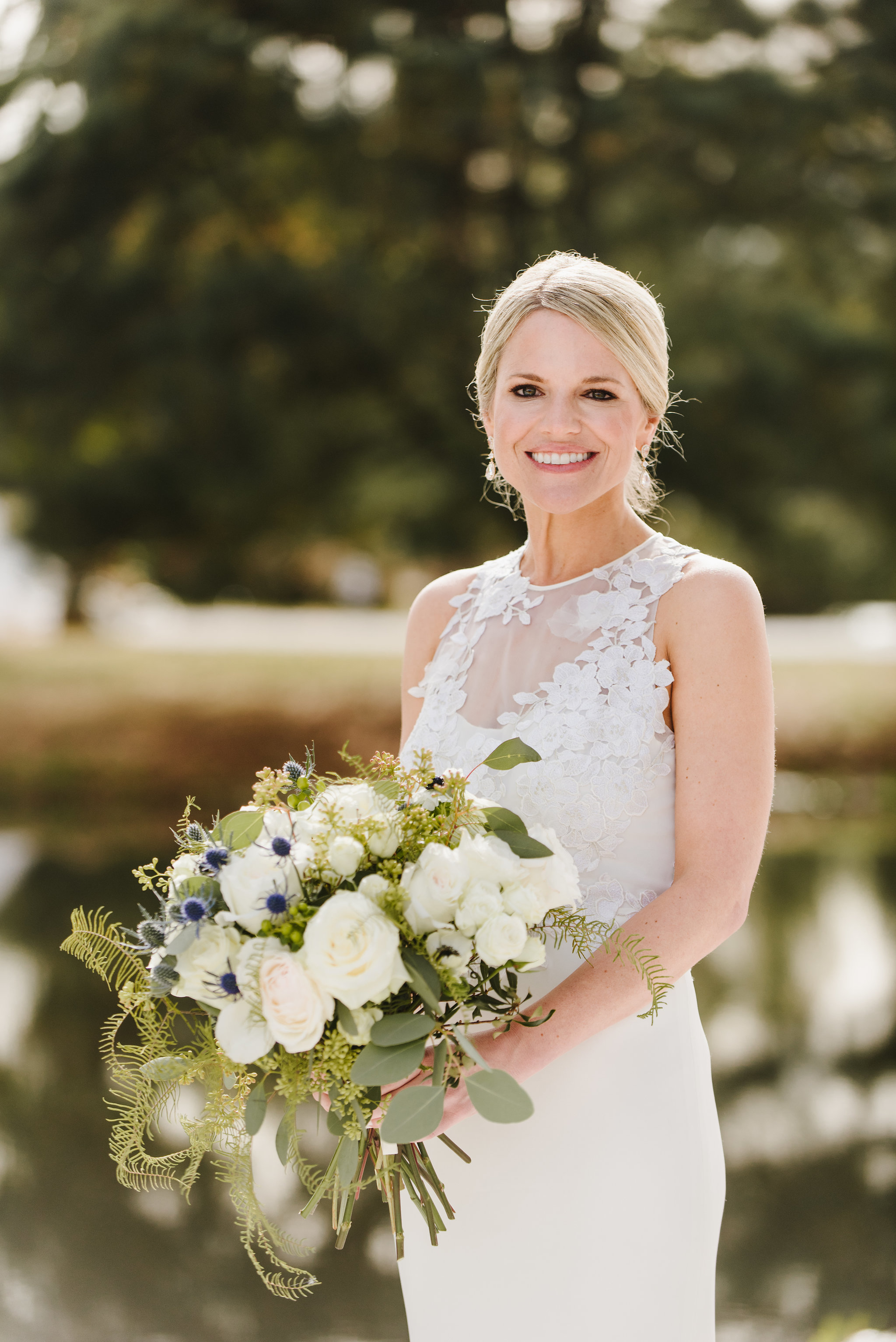 Bride holding large white bouquet created by Chesapeake Blooms, in front of water at the Historic Kent Manor Inn