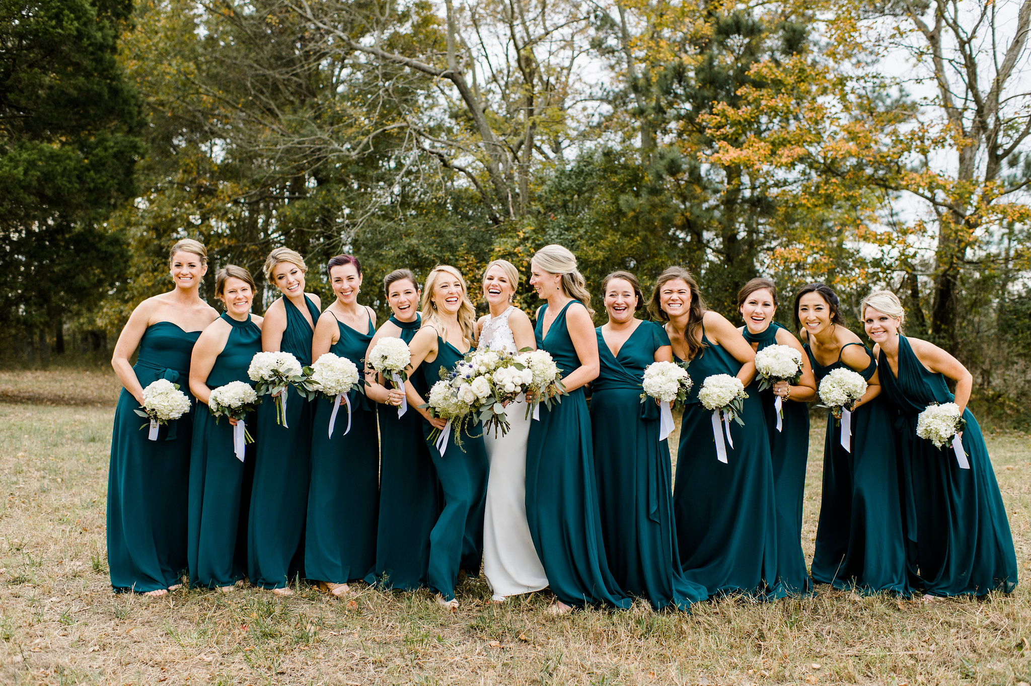 Bridesmaids with Bride wearing Teal dresses hold bouquets by Chesapeake Blooms