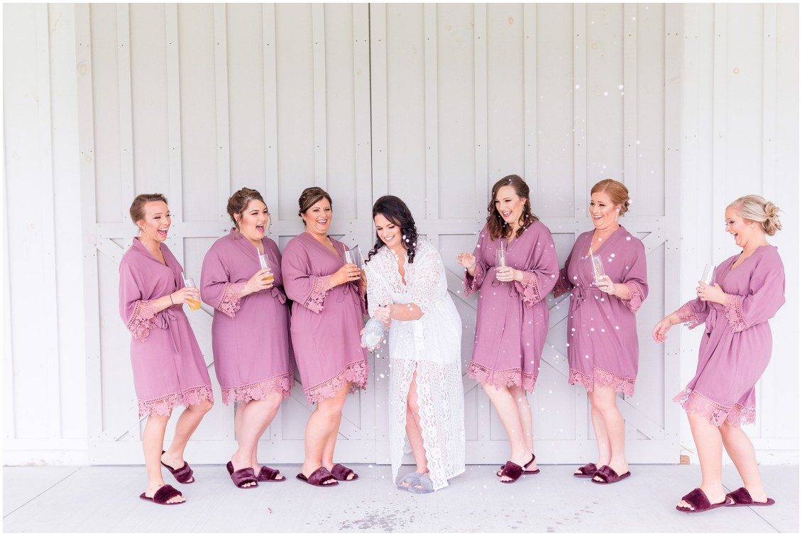 Matching fuchsia bridesmaids bathrobes and slippers. Bridal party popping champagne. | My Eastern Shore Wedding |