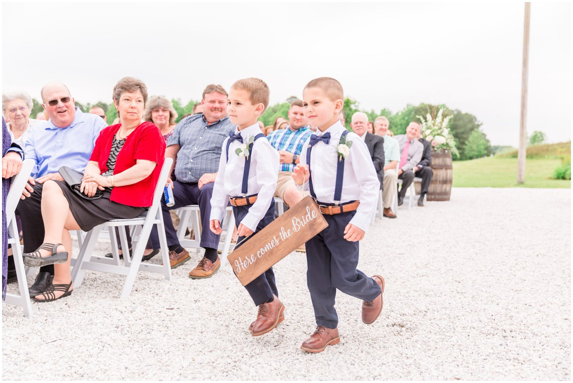"Pager boys carry a ""here comes the bride"" sign, walking down the aisle. 