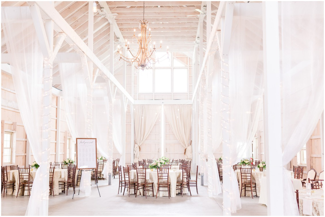 Kylan Barn wedding reception, large chandelier, white drapes hanging and wooden chairs. | My Eastern Shore Wedding |