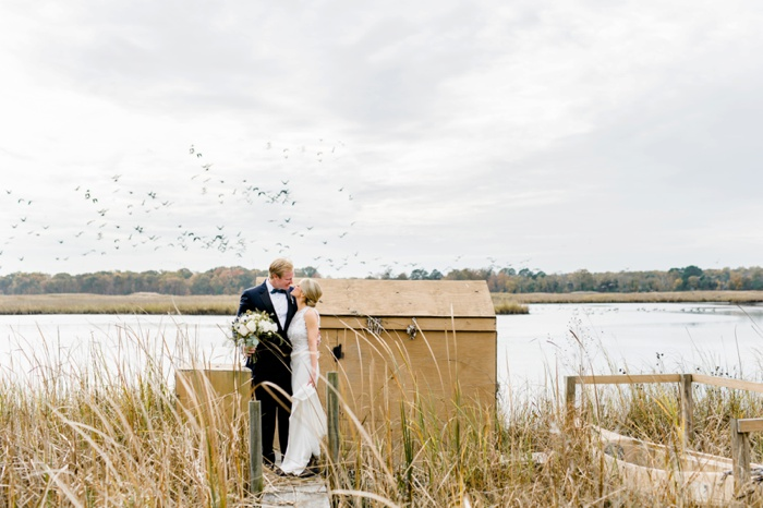 Bride and Groom kissing and holding large white bouquet created by Chesapeake Blooms on Maryland's Eastern Shore