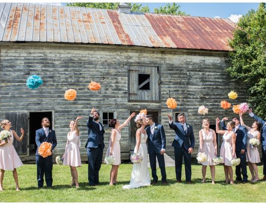 charming countryside wedding at the oaks waterfront inn and events in the summer - june - pink and blue wedding - photo of wedding party throwing colorful pompoms into the air - fun wedding photo idea