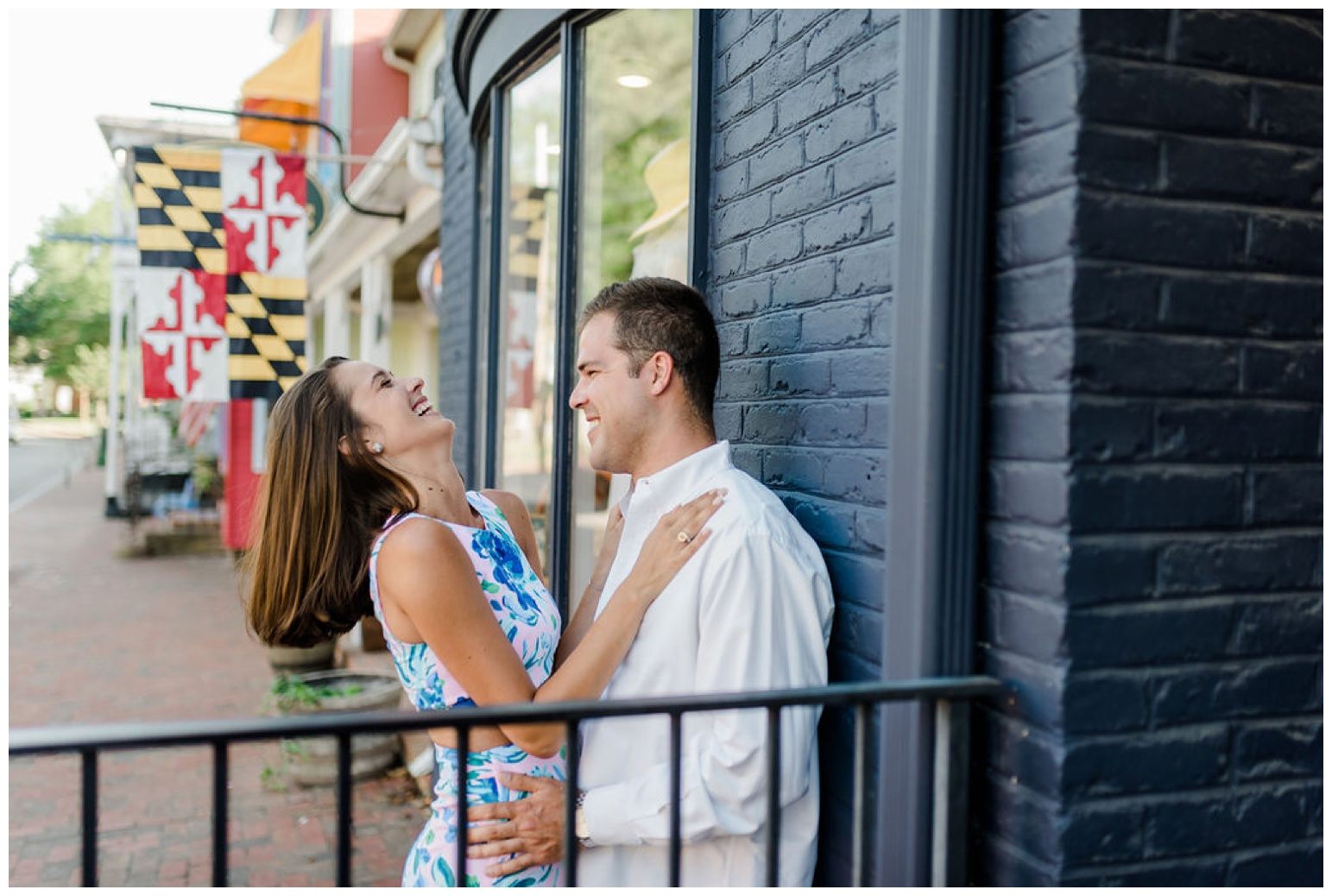 coastal maryland - engagement photos - shoot - inspiration and ideas - state flag - just engaged session at st. michaels - photo of couple laughing in front of building on talbot street