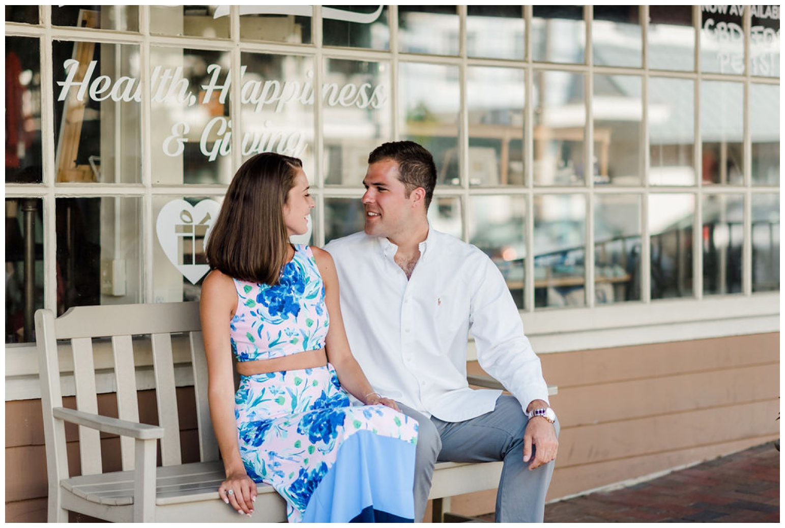 st. michaels engagement shoot - chesapeake bay inspired photo session - coastal maryland inspo full of oyster shells, sailboats, waterfront views from the dock and pier - photo of smiling couple in front of shop on talbot street | now featured on My Eastern Shore Wedding