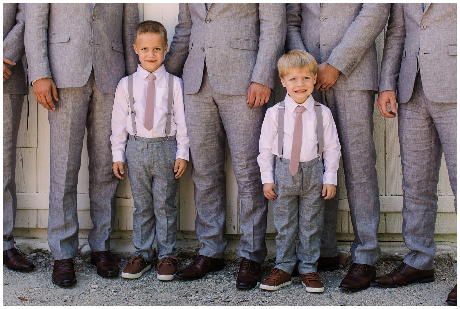 worsell manor wedding in the summer - warwick md - now featured on My Eastern Shore Wedding - coastal - sea - nautical - eastern shore - inspired wedding ideas and inspo - photo of groom and groomsmen - wedding party - in front of barn like wall door - white - formal portrait photo outdoors on maryland eastern shore - closeup of ring bearers and gray suits