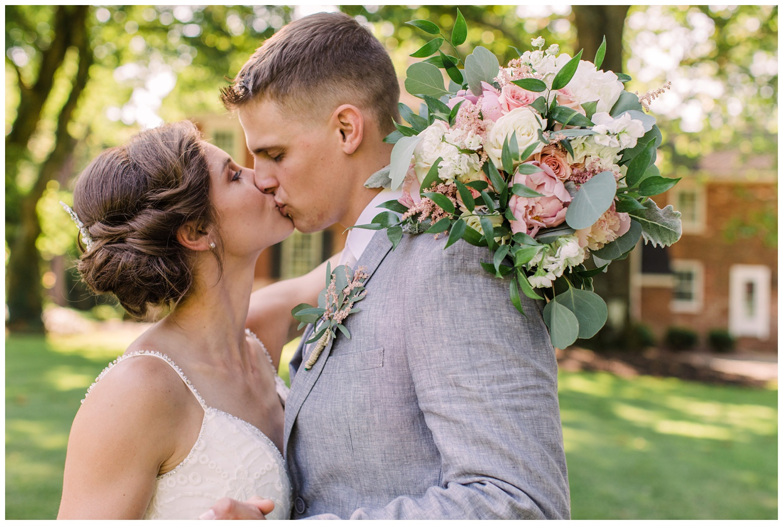 worsell manor wedding in the summer - warwick md - now featured on My Eastern Shore Wedding - coastal - sea - nautical - eastern shore - inspired wedding ideas and inspo - photo of bride and groom outdoors in front of brick manor style building - closeup - bridal bouquet - kissing