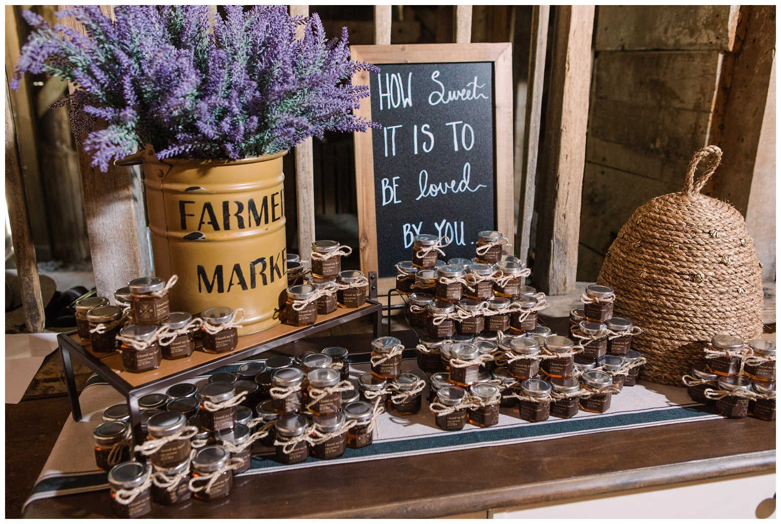 "honey bee theme - honey bee inspired - wedding ideas and inspiration - honey pot - real honey in jars - wedding favors - with bee balm flowers arrangement - chic basket bee hive with golden honey bees and ""how sweet it is to be loved by you"" sign in barn reception - rustic wedding decor ideas and inspiration"