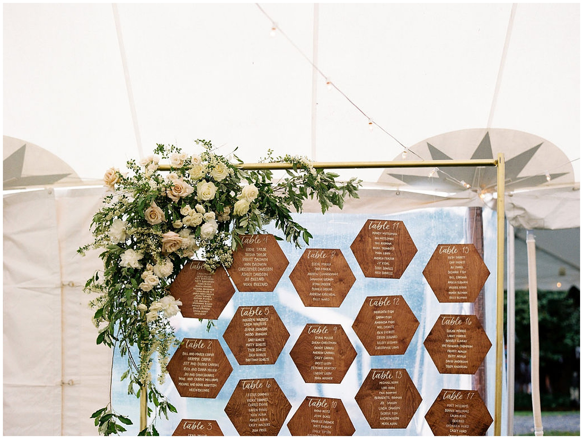 floral arbor arch with natural woodgrain geometric name card display; escort card, place card setting on metal gold frame; modern wedding decor with florals and timeless wedding theme on the eastern shore