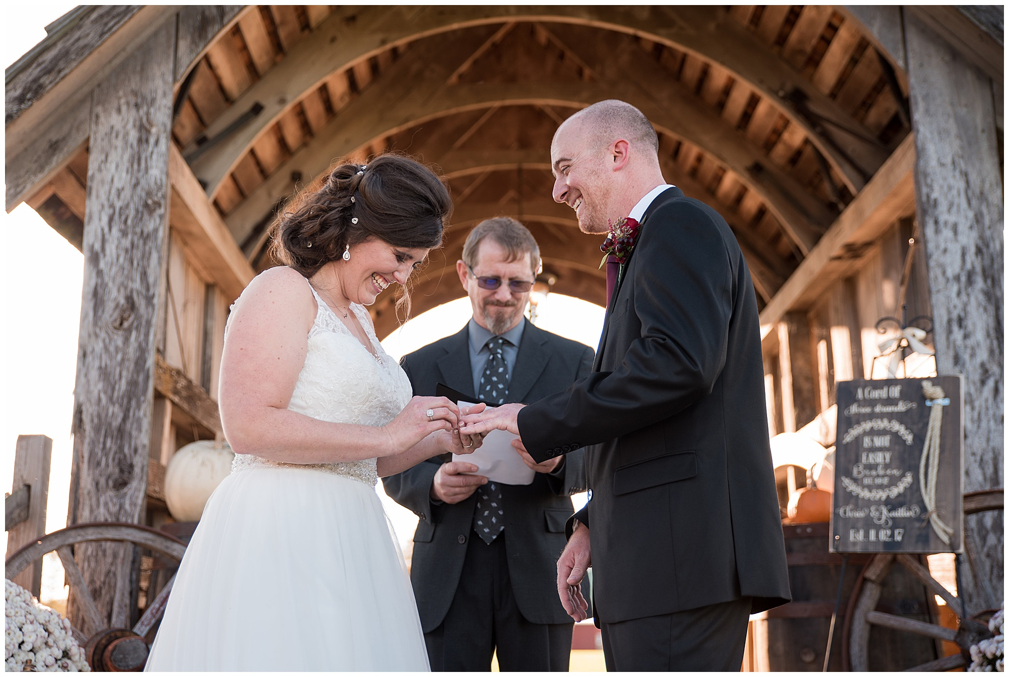 exchange of rings and huge smiles. wedding photos outdoors at covered bridge inn in lewes delaware. historic wedding barn venue on the eastern shore. fall wedding in november with rustic decor theme.