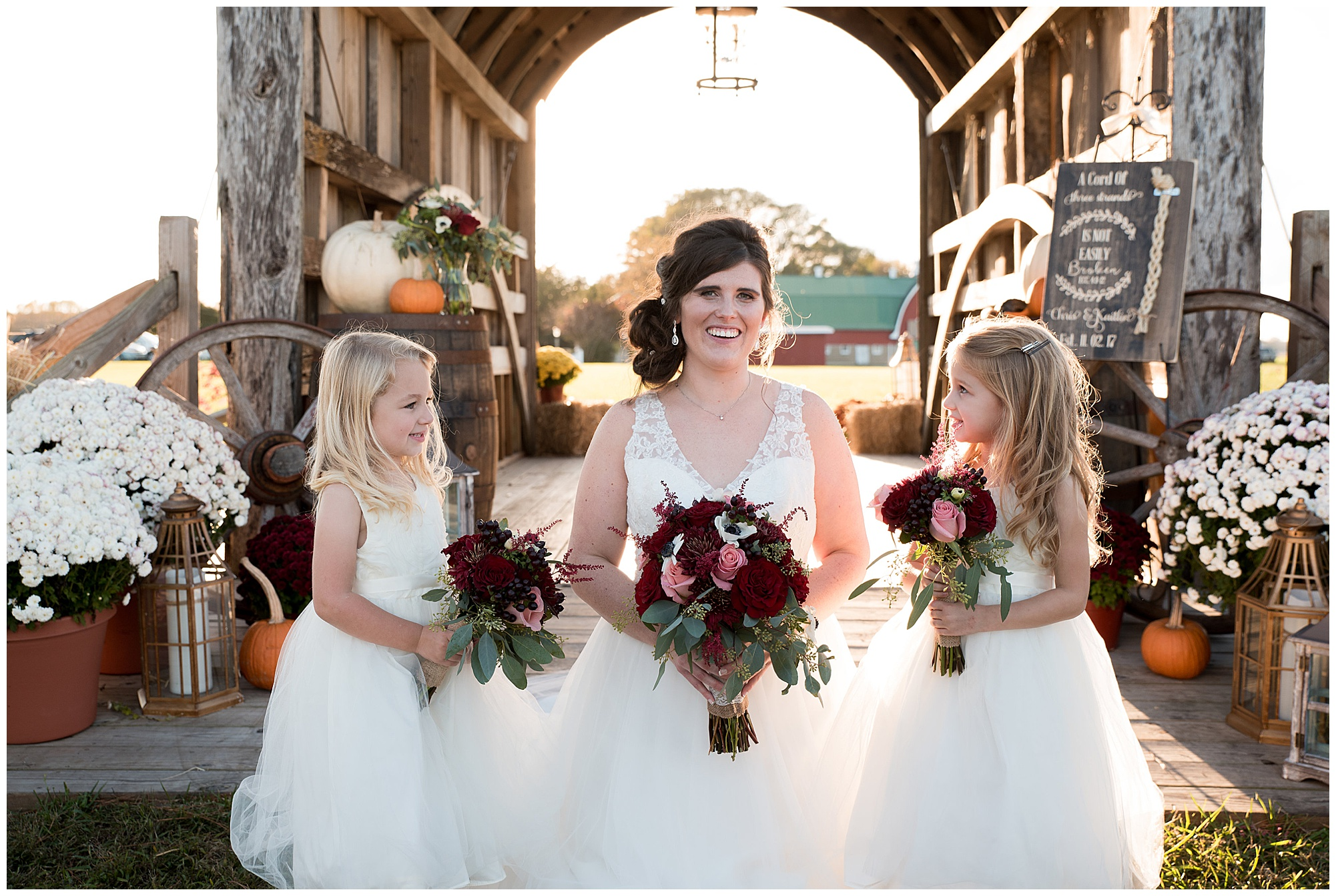 photo of bride and flower girls. wedding photos outdoors at covered bridge inn in lewes delaware. historic wedding barn venue on the eastern shore. fall wedding in november with rustic decor theme.