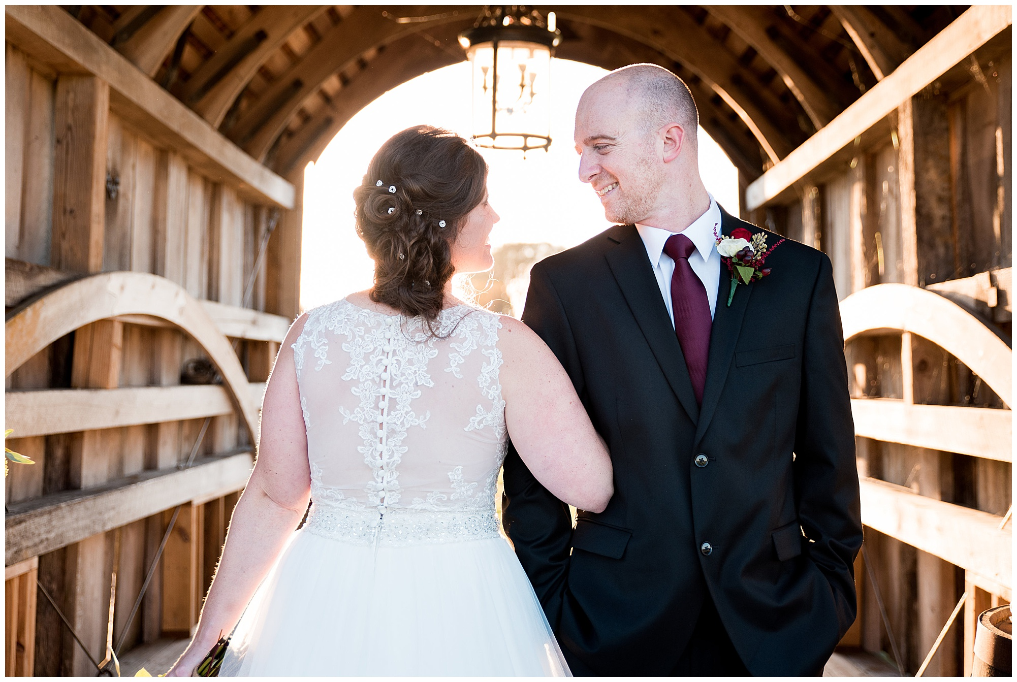 formal portraits outdoors in barn style covered bridge in delaware. happy couple smiling at each other linking arms.