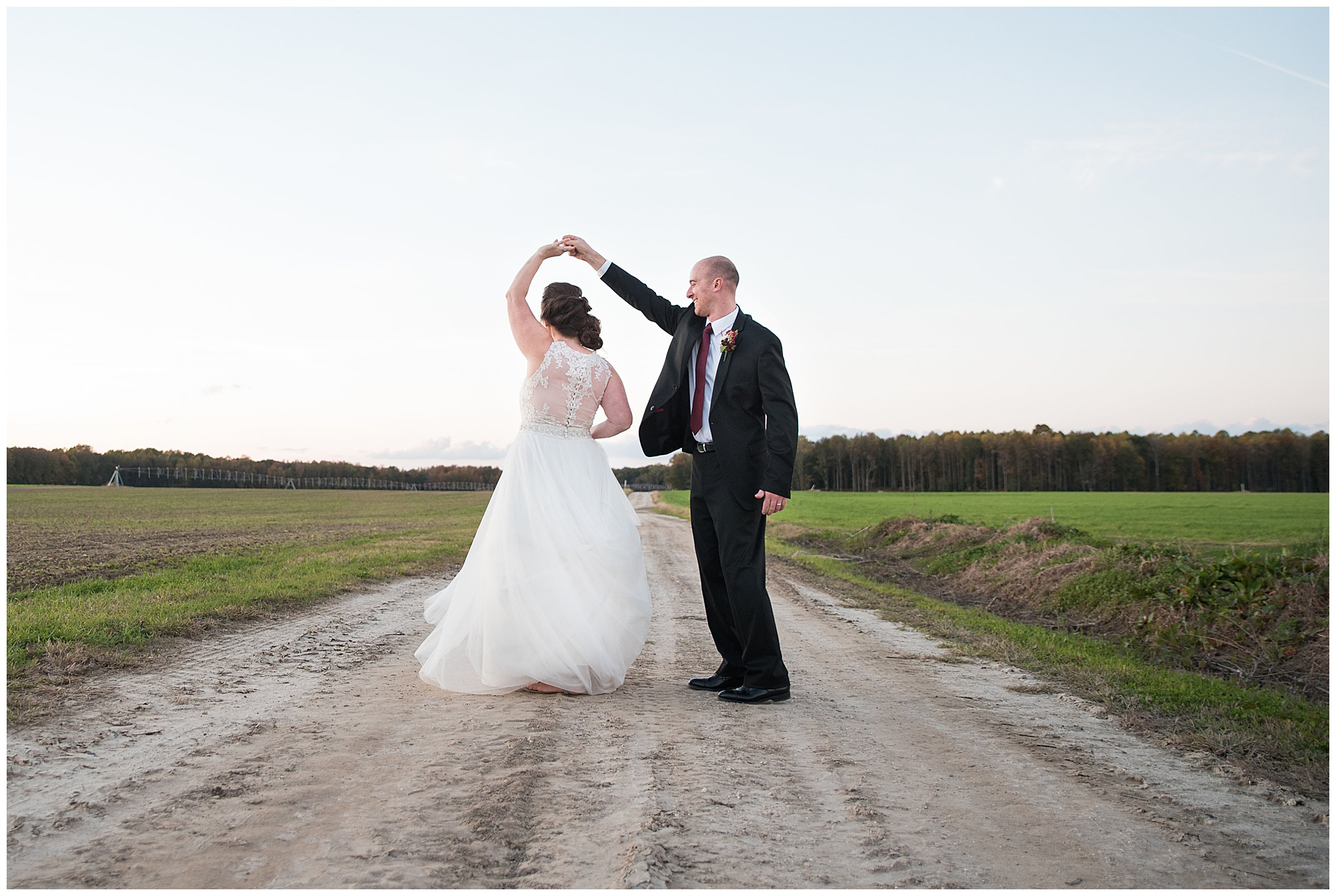 wedding photos at covered bridge inn bed and breakfast farm in lewes delaware. historic wedding barn venue on the eastern shore. fall wedding in november with rustic decor theme. couple twirling outdoors on dirt road on a farm wearing white wedding dress and black suit.