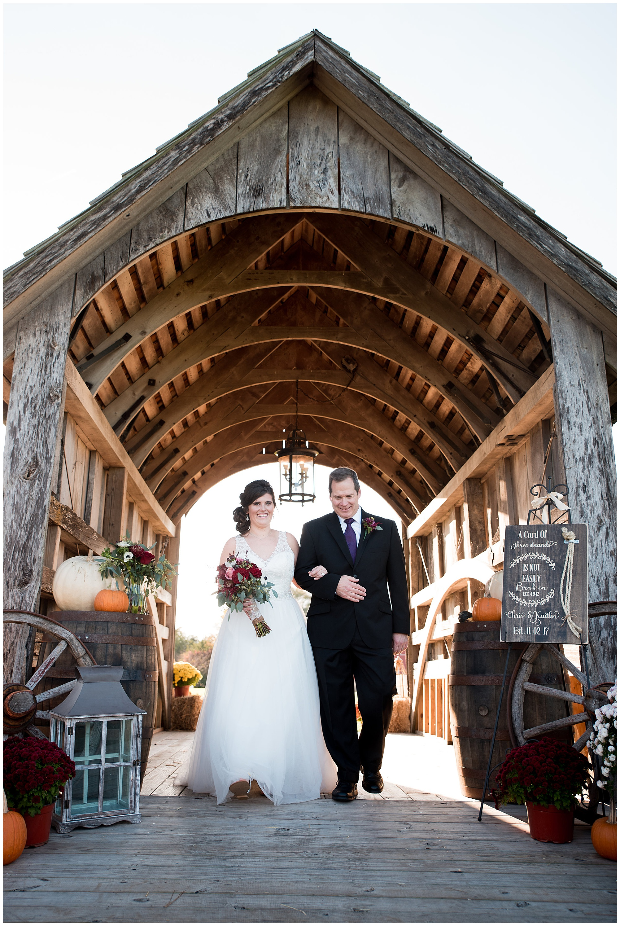 bride and father walking down the aisle. wedding photos outdoors at covered bridge inn in lewes delaware. historic wedding barn venue on the eastern shore. fall wedding in november with rustic decor theme.