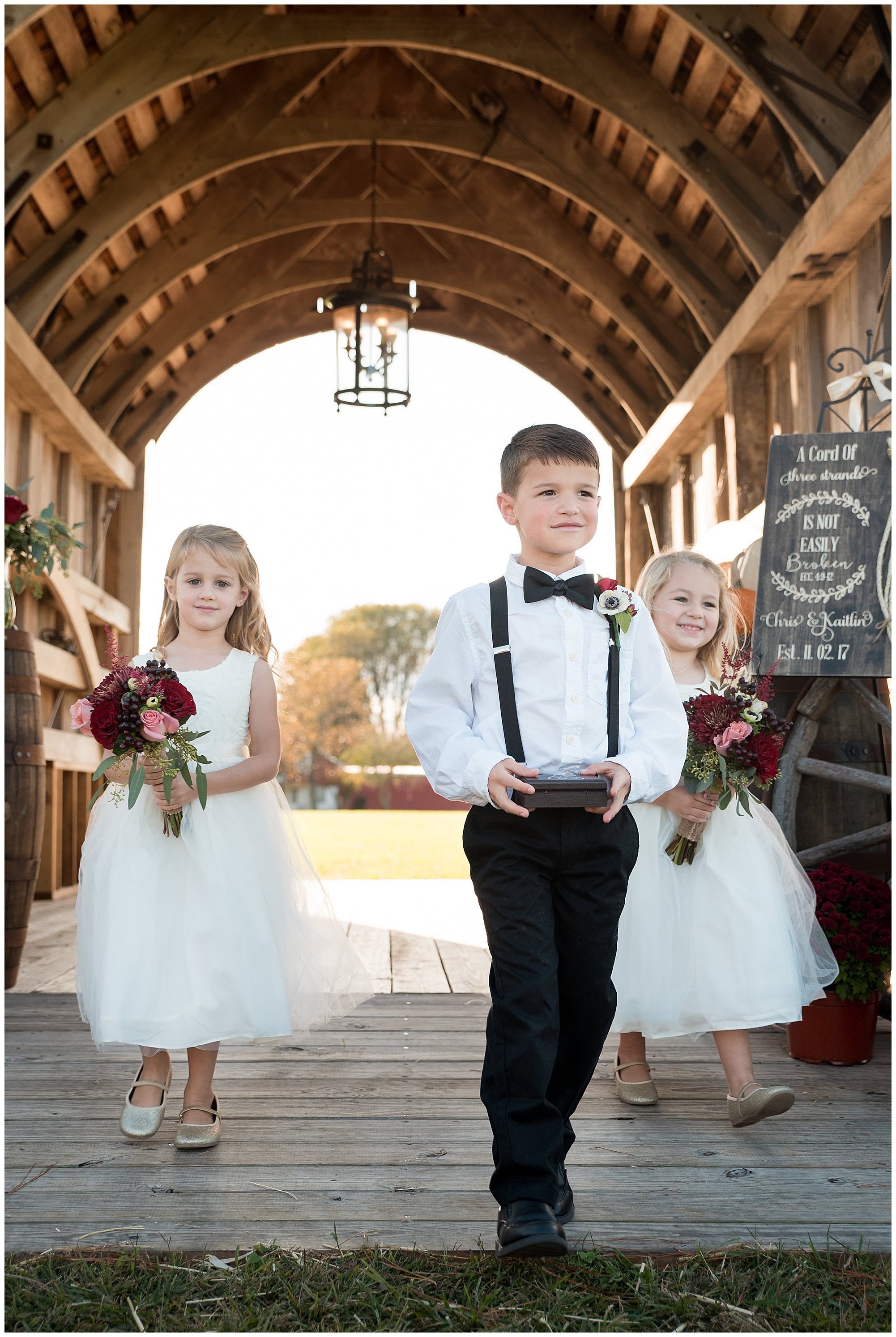 flower girls and ring bearer walking down the aisle. wedding photos outdoors at covered bridge inn in lewes delaware. historic wedding barn venue on the eastern shore. fall wedding in november with rustic decor theme.
