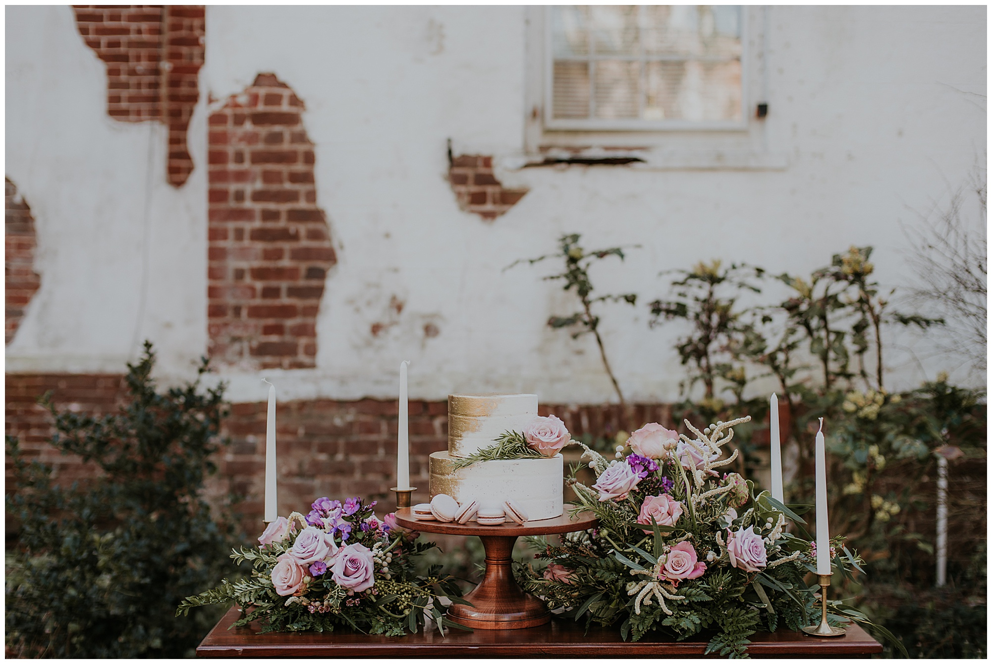 boho glam style inspo at chanceford hall wedding styled photoshoot. featured on my eastern shore wedding. wedding cake with roses, rosemary, candles display outdoors at historic maryland venue.