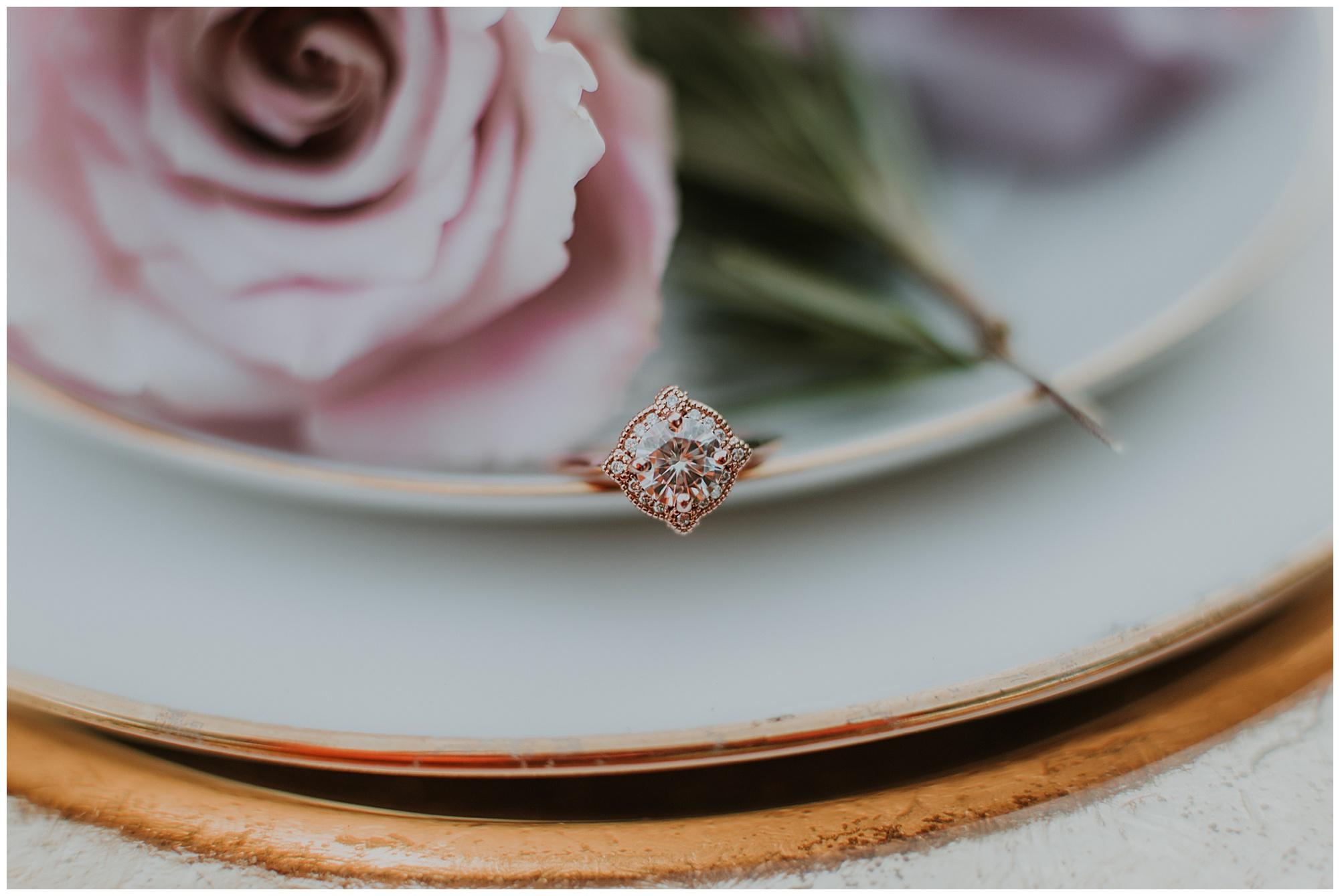 rose gold wedding ring with diamonds on gold guilded place setting. vintage inspired. elegant. roses.