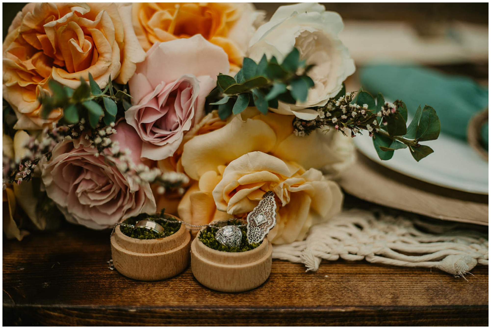 eco friendly and boho inspo with moss, rings, peach pink and yellow flowers, teal macrame and all natural accents and decor rustic table setting at carefree elopement at prancing deer farm maryland venue now featured on my eastern shore wedding