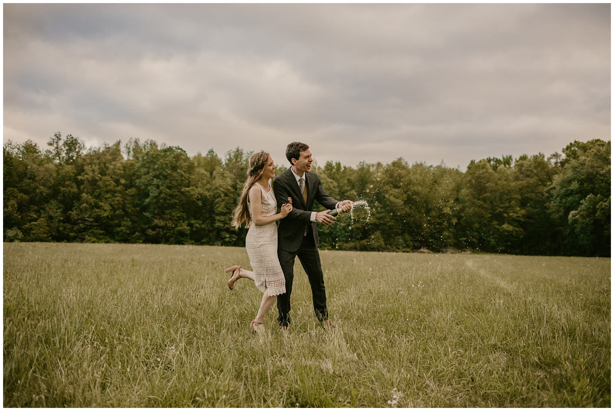 vintage lace cocktail wedding dress. gown. flower crown. outdoors. maryland eastern shore. couple laughing. running through field. popping champagne at prancing deer farm. outdoor green eco-friendly forest woodland venue in warwick maryland md