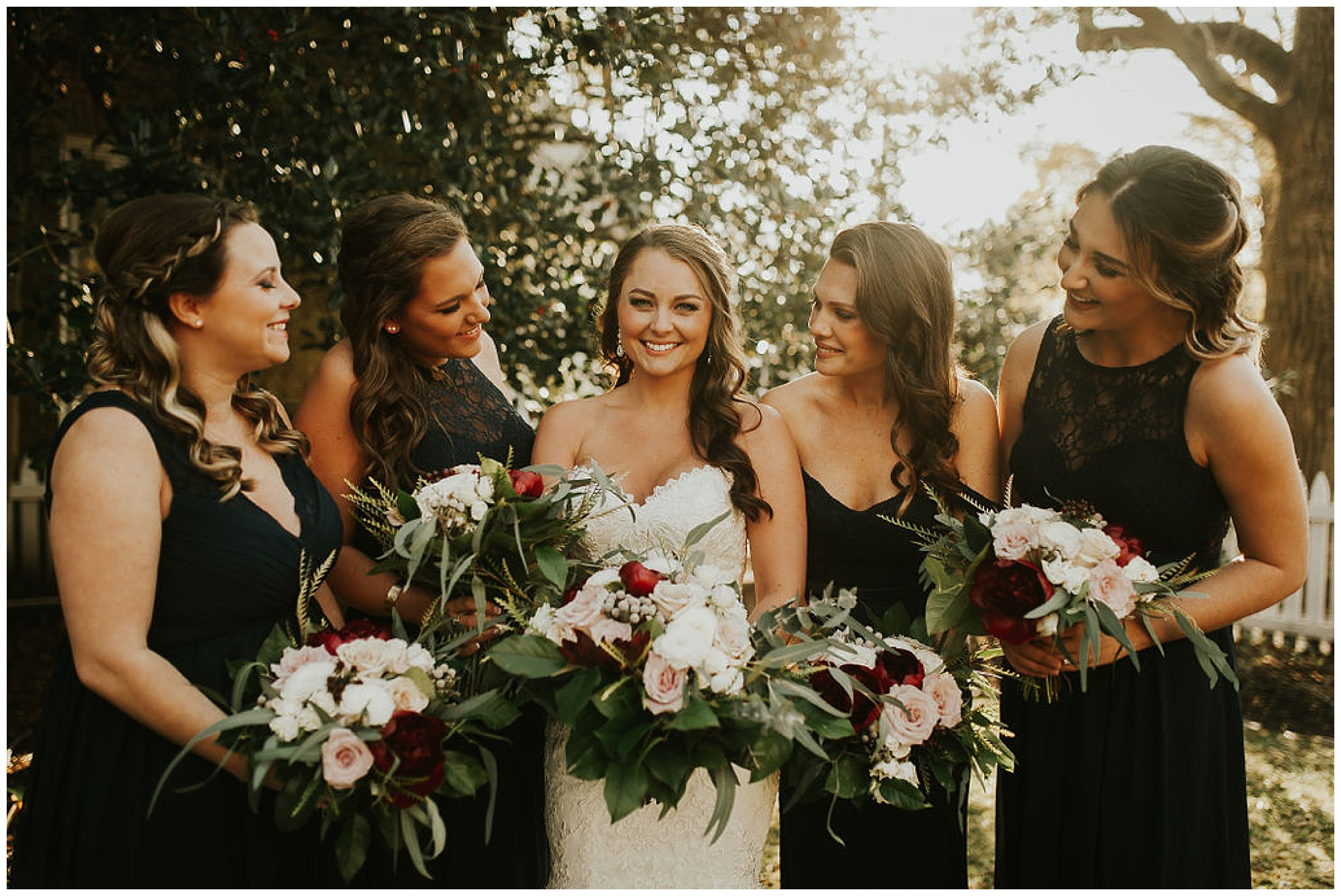 bride and bridesmaids wearing black mismatched dresses photo at the tidewater inn venue outdoors in easton maryland. autumn style fashion.
