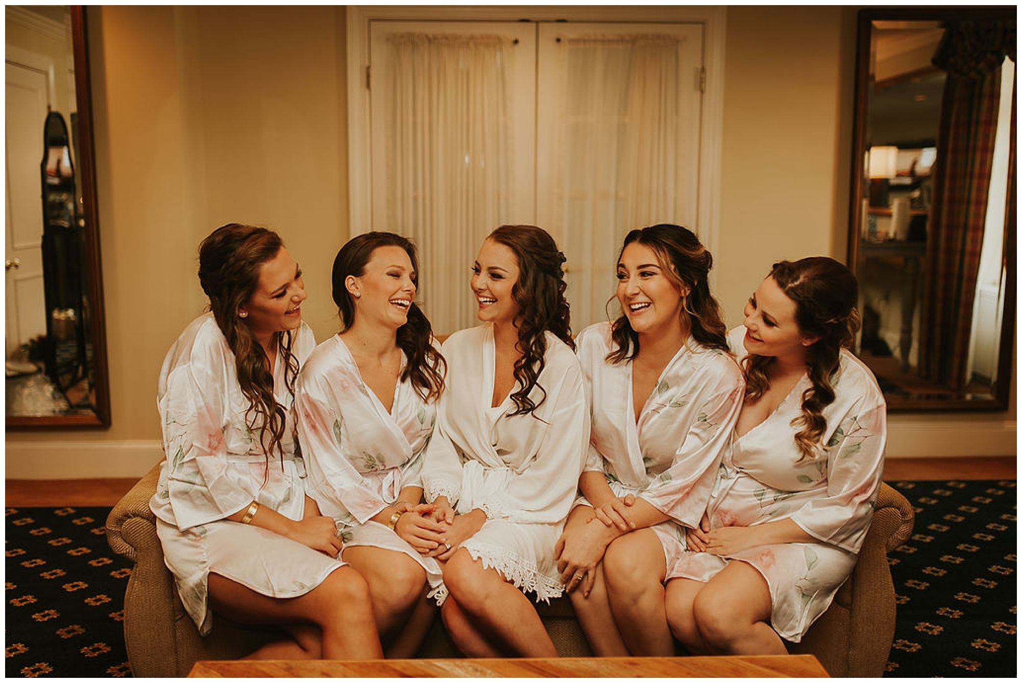 bride and bridesmaids laughing and smiling. wearing robes in tidewater inn venue in easton maryland. prewedding photo.