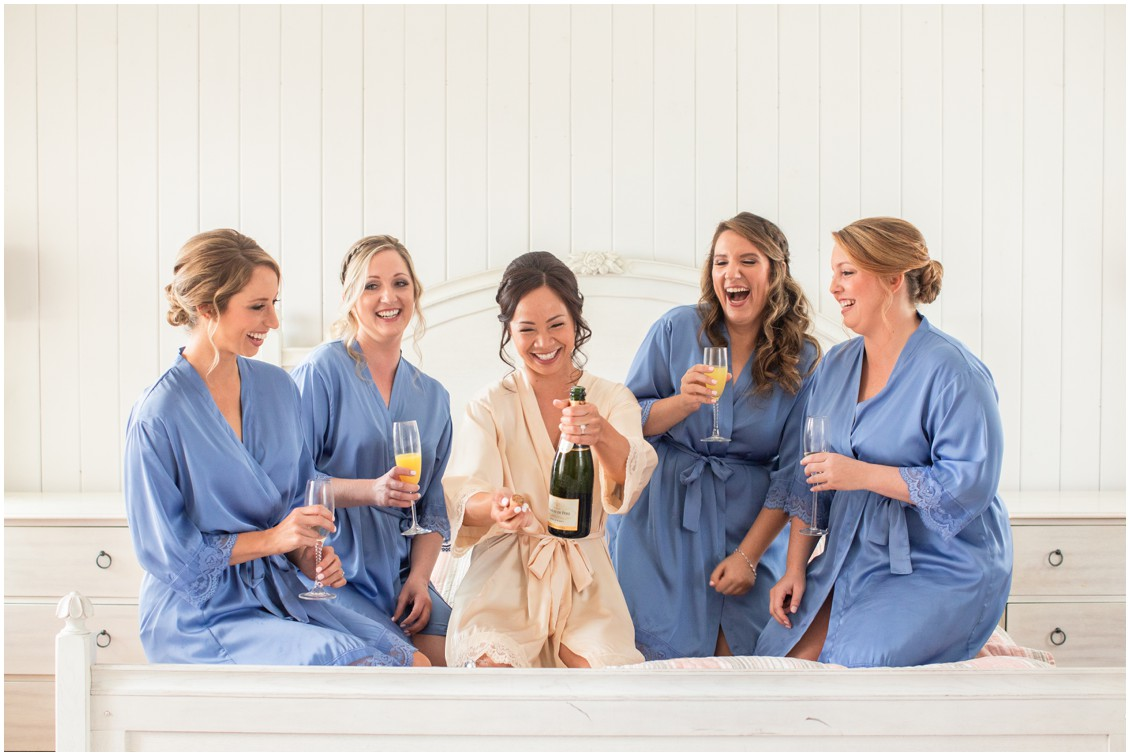 Bride and bridesmaids opening champagne |My Eastern Shore Wedding |Dover Tents and Events