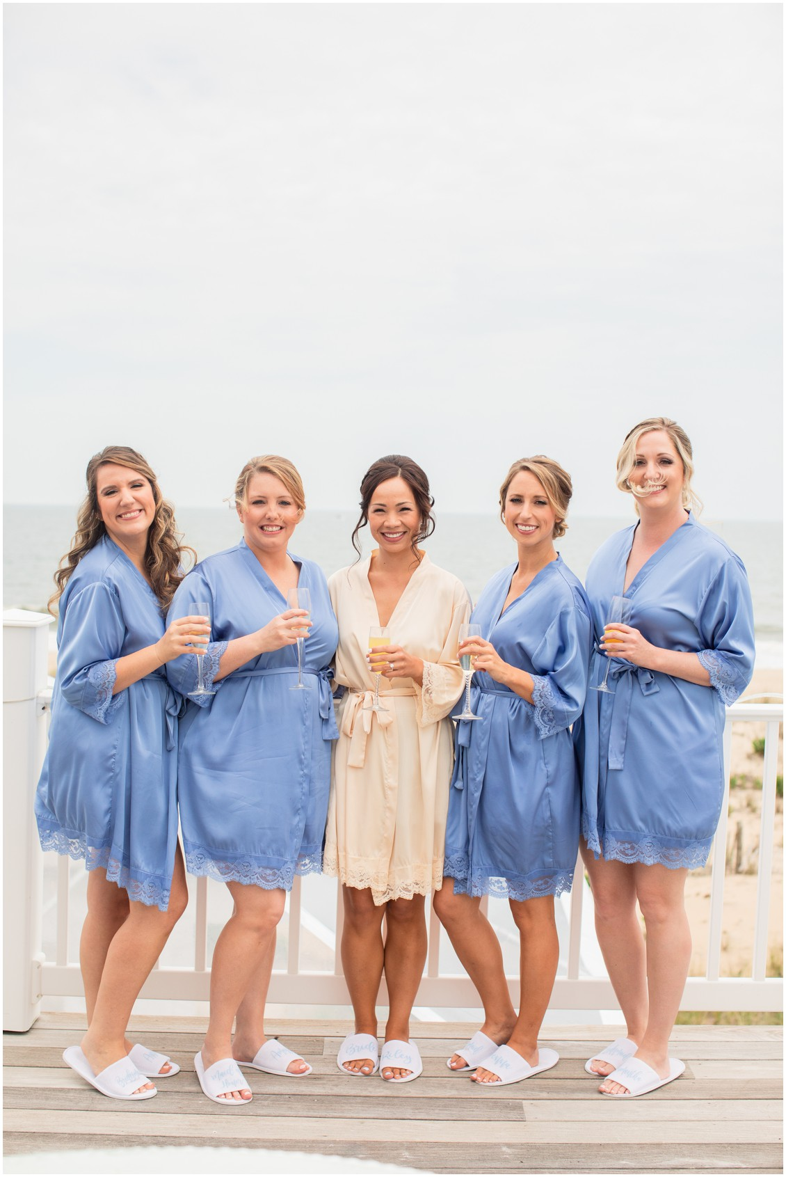 bride and bridesmaids with champagne in matching robes |My Eastern Shore Wedding |Dover Tents and Events