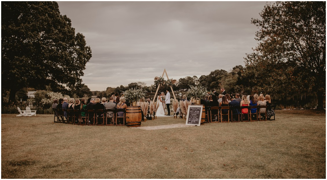 Bride and groom under triangular arch with pampas grass | My Eastern Shore Wedding | Sherwood Florist | Mill Street Farm