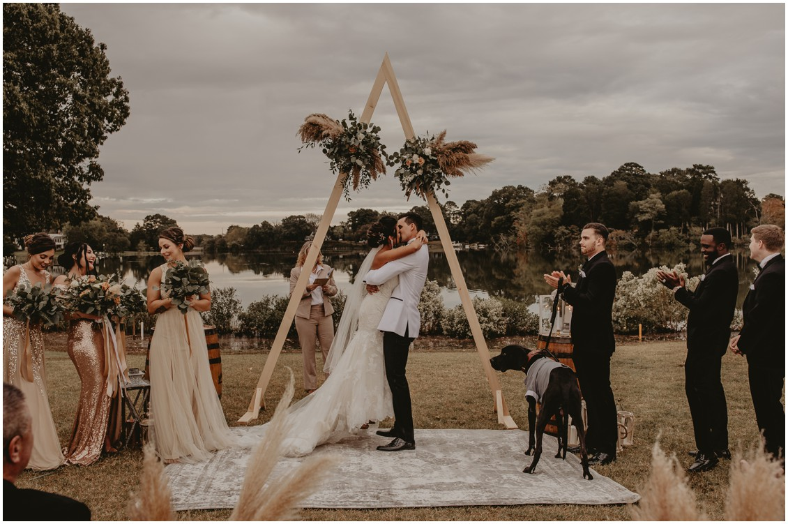 Bride and groom first kiss under triangular arch with pampas grass | My Eastern Shore Wedding | Sherwood Florist | Mill Street Farm