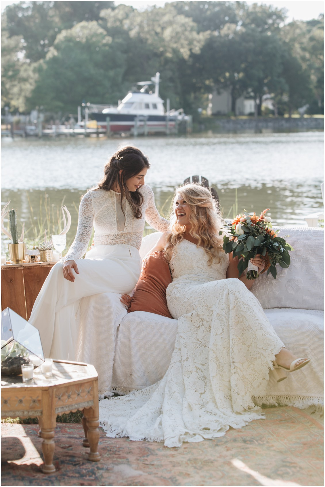 Brides on a sofa with river in the background at beautiful boho bash | My Eastern Shore Wedding | Sherwood Florist | Cecile Storm Photography