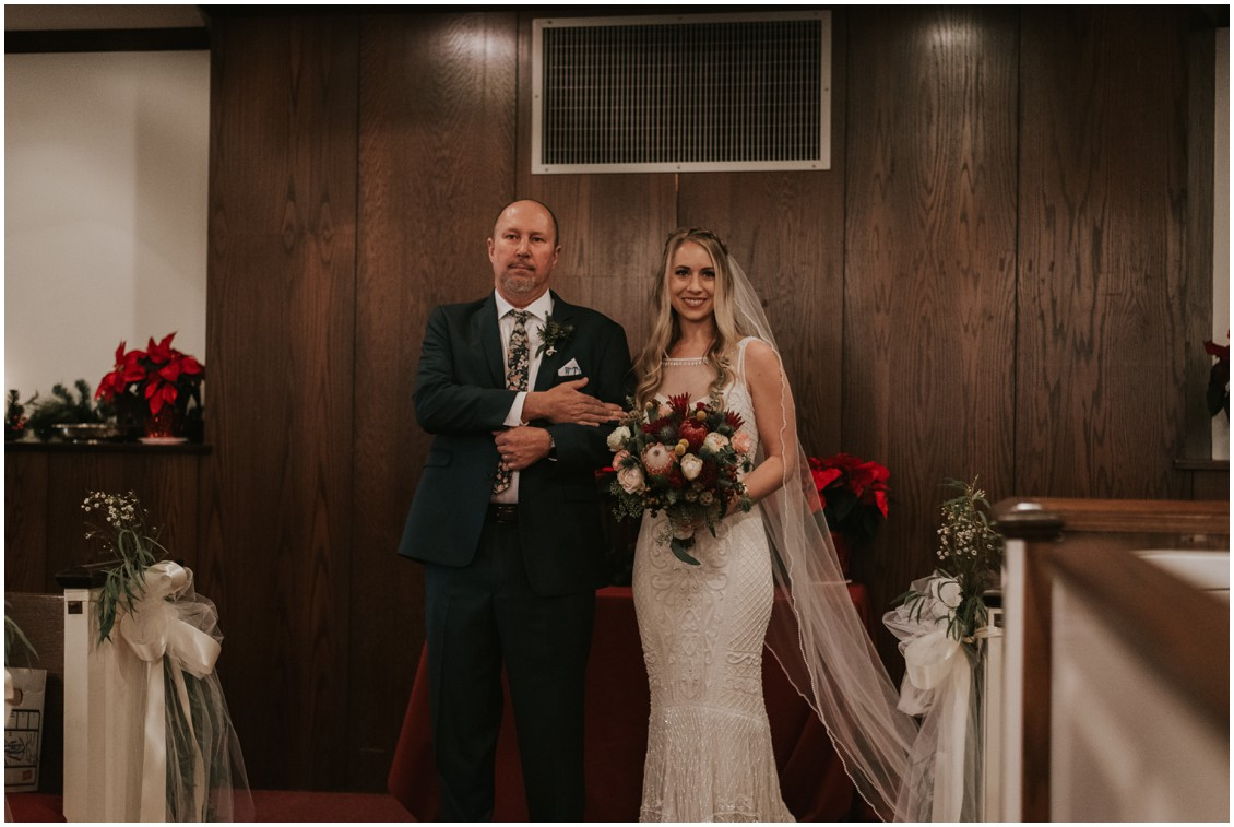 Bride and father getting ready to walk down church aisle with poinsettias winter wedding | My Eastern Shore Wedding | Bear Trap Dunes | Coastal Tented Events