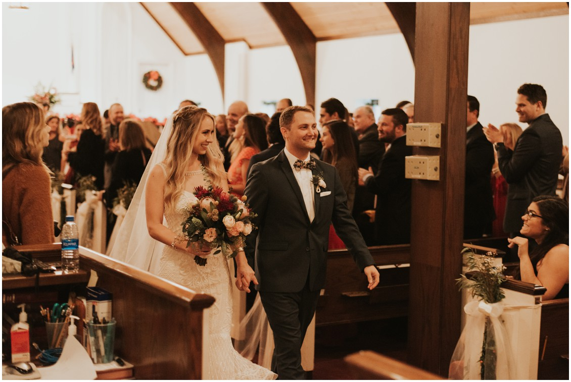 Bride and groom walking down aisle after ceremony in church in winter wedding  with poinsettias | My Eastern Shore Wedding | Bear Trap Dunes | Coastal Tented Events